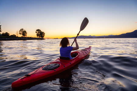 Girl Kayaking in Pacific Ocean during a vibrant golden sunny sunset. Taken in False Creek, Downtown Vancouver, British Columbia, Canada. 版權商用圖片