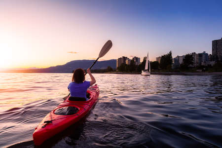 Girl Kayaking in a Modern City during a vibrant golden sunny sunset. Taken in False Creek, Downtown Vancouver, British Columbia, Canada.
