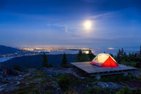 Camping Tent on top of a Mountain with Canadian Nature Landscape in the Background during colorful night after Sunset. Taken on Bowen Island, near Vancouver, British Columbia, Canada.