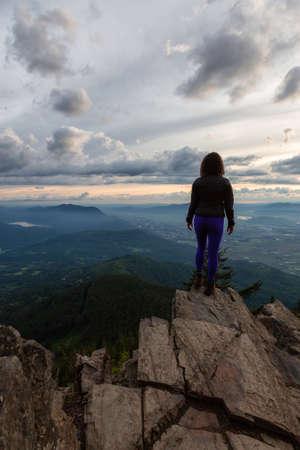 Fille aventureuse au sommet d'une montagne rocheuse surplombant le magnifique paysage naturel canadien pendant un coucher de soleil spectaculaire. Prises à Chilliwack, à l'est de Vancouver, Colombie-Britannique, Canada.
