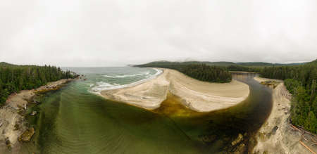 Aerial Panoramic View of a Beautiful Sandy Beach and a Lagoon on the Pacific Ocean Coast during a cloudy summer morning. Taken in Vancouver Island, British Columbia, Canada.