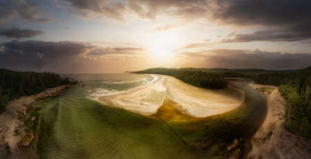 Aerial Panoramic View of a Beautiful Sandy Beach and a Lagoon on the Pacific Ocean Coast during a cloudy dramatic Sunset. Sky Composite. Taken in Vancouver Island, British Columbia, Canada.