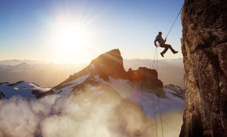 Epic Adventurous Extreme Sport Composite of Rock Climbing Man Rappelling from a Cliff. Mountain Landscape Background from British Columbia, Canada. Concept: Explore, Hike, Adventure, Lifestyle Banque d'images