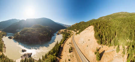 Beautiful Panoramic View of Canadian Nature and a Scenic Road, Trans-Canada Hwy, during sunny summer day. Aerial Drone Shot. Near Hells Gate, BC, Canada.