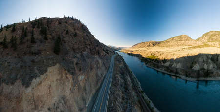 Scenic Road View surrounded by Dessert Hills, along Trans-Canada Highway, West of Kamloops, North of Lytton, British Columbia. Aerial Drone Shot. Stock fotó