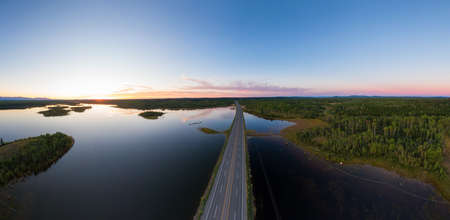 Picturesque Aerial View of Canadian Scenic Road surrounded by Peaceful Lakes. Vibrant summer sunset on the horizon. Cariboo Highway, Interior British Columbia.