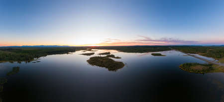 Picturesque Aerial View of Canadian Scenic Island surrounded by Peaceful Lakes. Vibrant summer sunset on the horizon. Cariboo Highway, Interior British Columbia.