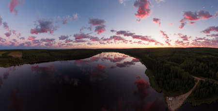 Peaceful Panoramic Aerial View of Calm Water at Sunrise on a Summer Morning. Cloudscape at Dawn, Reflecting on the Water. Inga Lake, Fort St. John, Alaska Highway, British Columbia.