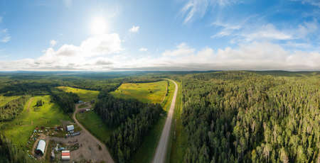 Scenic Panoramic Road View near Sunset surrouned by Forest, Farmland and Industry. Aerial Drone Shot. Northwest of Fort Nelson, Alaska Highway, Northern British Columbia.