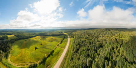Scenic Panoramic Road View near Sunset surrouned by Forest, Farmland and Nature. Aerial Drone Shot. Northwest of Fort Nelson, Alaska Highway, Northern British Columbia.