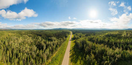 Scenic Panoramic Road View near Sunset surrouned by Forest, Nature and Mountains. Aerial Drone Shot. Northwest of Fort Nelson, Alaska Highway, Northern British Columbia. Stock fotó