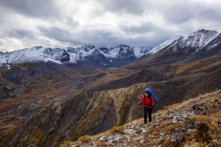 Girl Backpacking along Scenic Hiking Trail surrounded by Mountains in Canadian Nature. Taken in Tombstone Territorial Park, Yukon, Canada. 스톡 콘텐츠