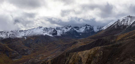Beautiful Panoramic View of Scenic Landscape and Snowy Mountains in Canadian Nature. Season change from Fall to Winter. Aerial Shot. Taken near Grizzly Lake in Tombstone Territorial Park, Yukon, Canada. 写真素材