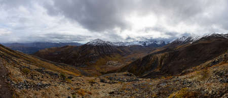 Panoramic View of Scenic Landscape, Valley and Mountains in Canadian Nature. Season change from Fall to Winter. Taken in Tombstone Territorial Park, Yukon, Canada.