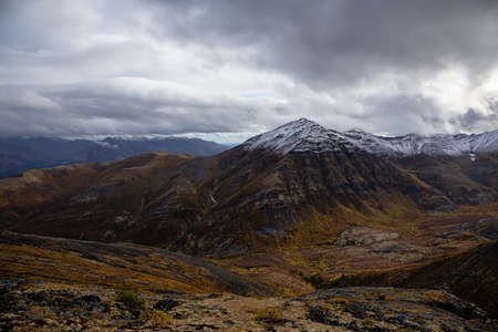 View of Scenic Landscape, Valley and Mountains in Canadian Nature. Season change from Fall to Winter. Taken in Tombstone Territorial Park, Yukon, Canada.