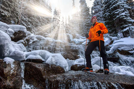 Adventure man standing besides a beautiful waterfall in the winter wilderness. Sunrays. Taken in Joffre Lakes, North of Vancouver, British Columbia, Canada. Concept: Adventure, holiday