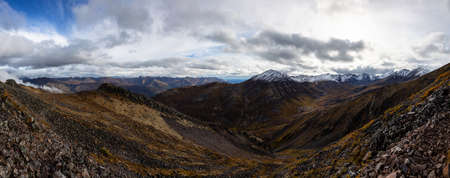 Beautiful Panoramic View of Scenic Mountains and Rocky Landscape in Canadian Nature. Season change from Fall to Winter. Taken in Tombstone Territorial Park, Yukon, Canada.