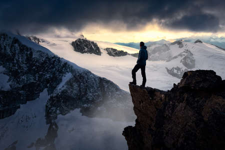 Man Hiker on top of a Mountain Peak. Dreamscape Artistic Render Composite. Landscape background from British Columbia, Canada. Dark Dramatic Sunset Sky.