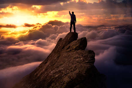 Fantasy Adventure Composite with a Man on top of a Mountain Cliff with Dramatic Cloudscape in Background during Sunset or Sunrise. Concept: Hike, Freedom, Explore, Journey