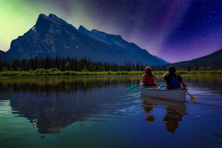 Couple adventurous friends are canoeing in a lake surrounded by the Canadian Mountains. Night Sky with Stars and Aurora Lights Artistic Render. Taken in Vermilion Lakes, Banff, Alberta, Canada. Banco de Imagens