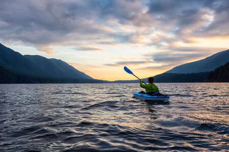 Beautiful View of Person Kayaking on Scenic Lake at Sunset surrounded by Mountains in Canadian Nature. Taken in Golden Ears Provincial Park, near Vancouver, British Columbia, Canada. Banque d'images