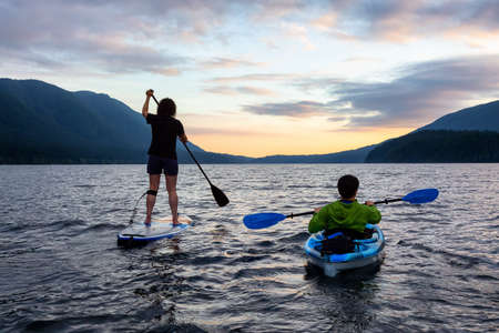 Friends on Scenic Lake Kayaking and Paddleboarding Together in Canadian Nature. Taken in Golden Ears Provincial Park, British Columbia.