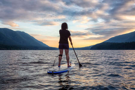 Woman Paddleboarding on Scenic Lake at Sunset in Canadian Nature. Taken in Golden Ears Provincial Park, British Colmbia, Canada.
