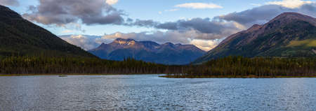 Panoramic View of Scenic Lake surrounded by Mountains and Trees on a Cloudy Morning at Sunrise in Canadian Nature. Taken in Northern British Columbia, Canada. Zdjęcie Seryjne