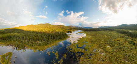 Peaceful Panoramic Lake View from Above at Sunset, surrounded by Lush, Green Forest in Canadian Nature. Aerial Drone Shot. Taken near Alaska Highway, Southern Yukon, Canada. Banco de Imagens