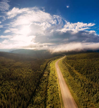 Beautiful View of Scenic Road from Above surrounded by Lush Forest, Clouds and Mountains. Aerial Drone Shot. Alaska Highway, West of Fort Nelson. Northern Rockies, British Columbia, Canada.