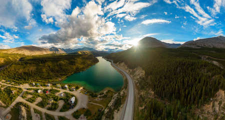 Gorgeous Panoramic View of Glacial Lake surrounded by Scenic Road at Sunset. Aerial Drone Shot. Northern Rocky Mountains, British Columbia, Canada.