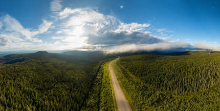 Beautiful Panoramic View of Scenic Road from Above surrounded by Lush Forest and Mountains. Aerial Drone Shot. Alaska Highway, West of Fort Nelson. Northern Rockies, British Columbia, Canada.