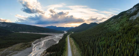 Beautiful Panoramic View of Scenic Road by Glacial River at Sunset. Aerial Drone Shot. Northern Rocky Mountains, British Columbia, Canada. 免版税图像