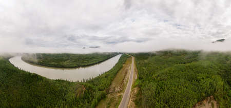 Beautiful Panoramic View of Winding River surrounded by Canadian Nature. Aerial Drone Shot. Taken from the Alaska Highway in Northern British Columbia, Canada. 免版税图像