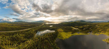 Stunning Panoramic View of Serene Lakes surrounded by Beautiful Trees at Sunset in Canadian Nature. Taken near Alaska Highway. Aerial Drone Shot. Southern Yukon, Canada.