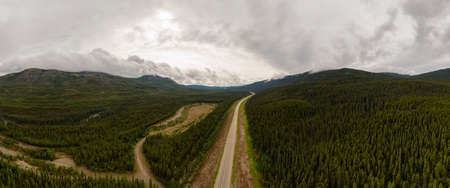 Picturesque Panoramic View of Scenic Road from Above surrounded by Mountains and Forest. Aerial Drone Shot. Taken on the Alaska Highway, Southern Yukon, Canada.