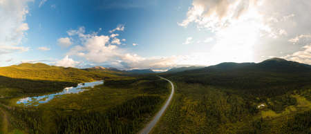 Beautiful Panoramic View of Scenic Road surrounded by Forest, Lake and Mountains at Sunset. Aerial Drone Shot in Canadian Nature. Taken by Alaska Highway, Southern Yukon, Canada.