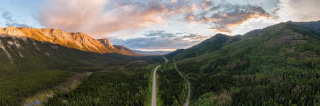 Picturesque Panoramic View of Scenic Highway surrounded by Golden Rocky Mountains at Sunset in Canadian Nature. Aerial Drone Shot. Alaska Highway, near Tagish, Southern Yukon, Canada.