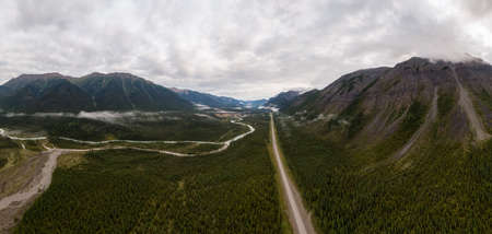 Picturesque Panoramic View of Scenic Road from Above alongside Winding Glacial River. Aerial Drone Shot. Alaska Highway in the Northern Rockies, British Columbia, Canada. 免版税图像