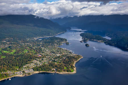 Aerial view of an Ocean Inlet in a modern city during a cloudy morning. Taken in Deep Cove, Vancouver, British Columbia, Canada.