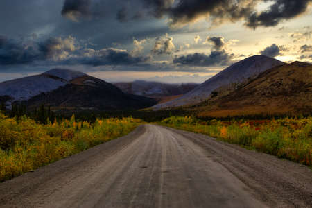 View of Scenic Road and Mountains on a Fall Day in Canadian Nature. Dramatic Sunset Sky Artistic Render. Taken near Tombstone Territorial Park, Yukon, Canada.