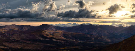 Aerial Panoramic View of Scenic Landscape and Mountains on a Cloudy Fall Season in Canadian Nature. Colorful Sunrise Sky Artistic Render. Taken in Tombstone Territorial Park, Yukon, Canada. Stock Photo