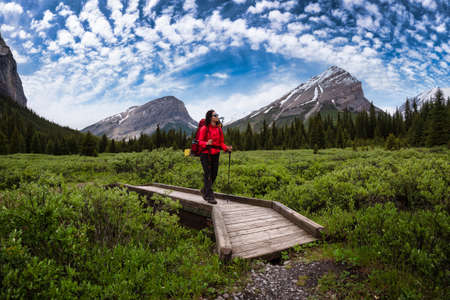 Female Backpacker Hiking in Canadian Rockies. Colorful Blue Sky Art Render. Taken near Banff, boarder of British Columbia and Alberta, Canada. Concept: Explore, Adventure, Trekking, Backpacking Banque d'images
