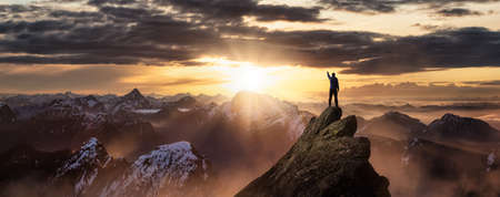 Magical Fantasy Adventure Composite of Man Hiking on top of a rocky mountain peak. Background Landscape from British Columbia, Canada. Sunrise Dramatic Colorful Sky