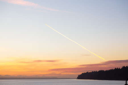 Airplane cloud trail in the sky during a colorful sunset in Whiterock, Vancouver, British Columbia, Canada. 版權商用圖片