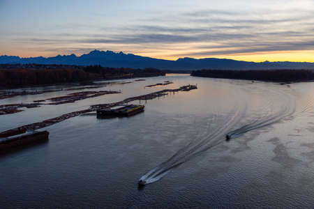 Aerial View of Fraser River. Dramatic Colorful Sunrise Sky. Taken over Port Mann Bridge in Surrey, Vancouver, British Columbia, Canada.