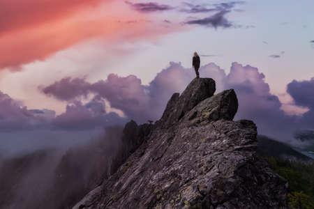 Adventurous Girl on top of a rugged rocky mountain. Dramatic Colorful Sunrise Sky Art Render. Taken on Crown Mountain, North Vancouver, BC, Canada.