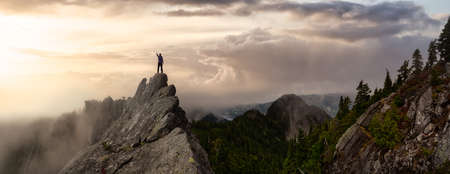 Adventurous Man on top of a rugged rocky mountain. Dramatic Colorful Sunrise Sky Art Render. Taken on Crown Mountain, North Vancouver, BC, Canada.