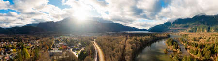 Aerial panoramic view of a small town with Chief Mountain in the background during a sunny sunrise. Taken in Squamish, North of Vancouver, British Columbia, Canada. 版權商用圖片