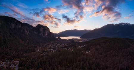 Squamish, North of Vancouver, British Columbia, Canada. Beautiful Aerial Panoramic View of a small town surrounded by Canadian Nature during Autumn Season. Dramatic Sunset Sky. 版權商用圖片